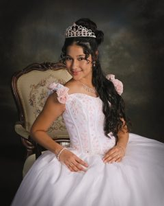 Quinceanera in White Gown and Pink Roses wearing a Pink Tiara