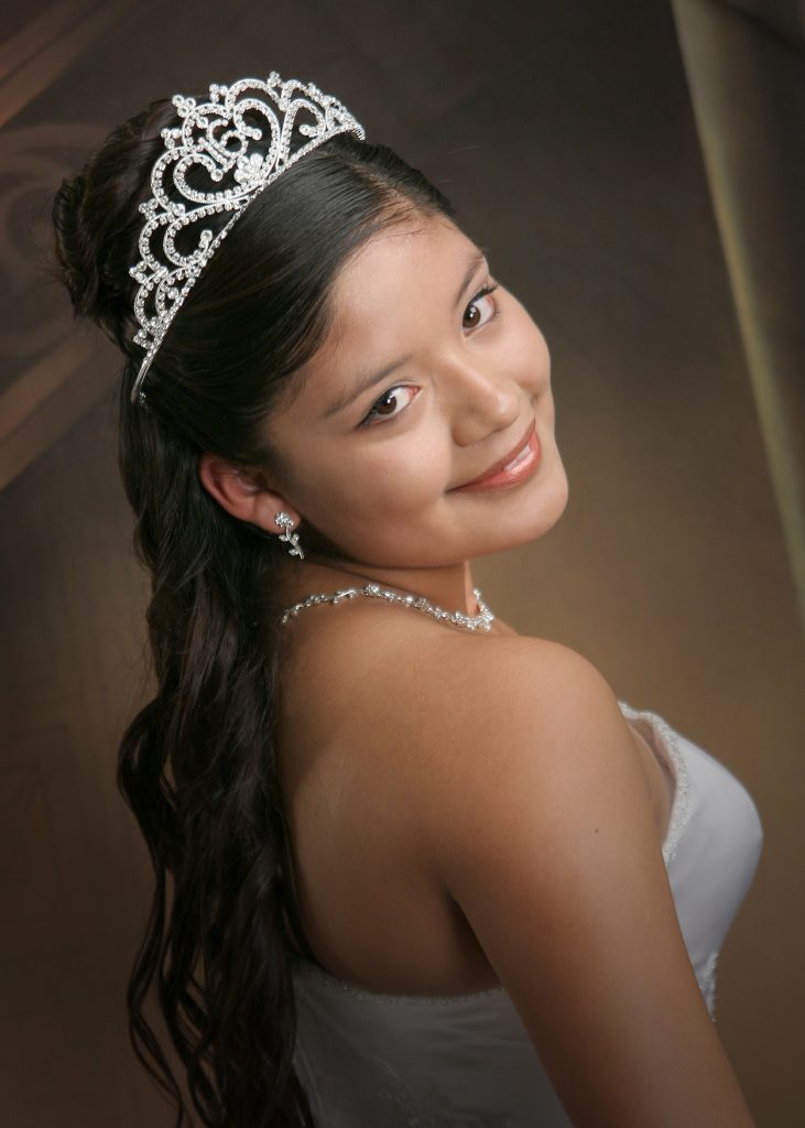 Quinceanera in White Gown wearing a silver tiara with the number 16